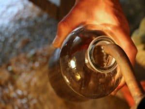 Après de longues heures de distillation, Laurent récupère les précieuses huiles essentielles.