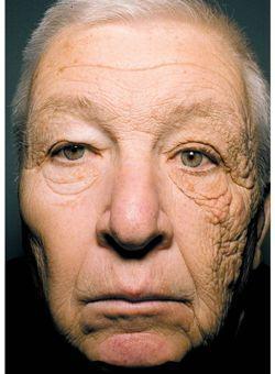 Visage d'un homme dont une partie de son visage était exposé au soleil derrière une vitre dans son bureau.
